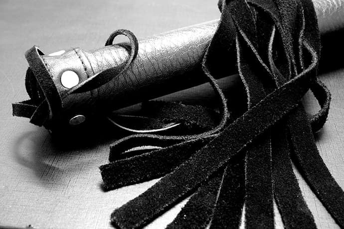 black suede flogger lying on table