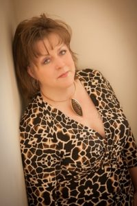 Leaning against wall in leopard print dress