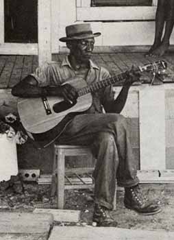 Delta blues man strumming guitar on shack porch